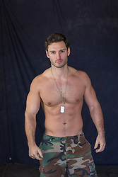 Shirtless hunky man in army pants and dog tags