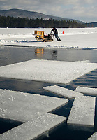 Sawyer Dave Lacasse manuevers the antique saw into place as he cuts ice blocks for Rockywald Deephaven Camp's two ice houses during their annual ice harvest on Wednesday.    (Karen Bobotas/for the Laconia Daily Sun)