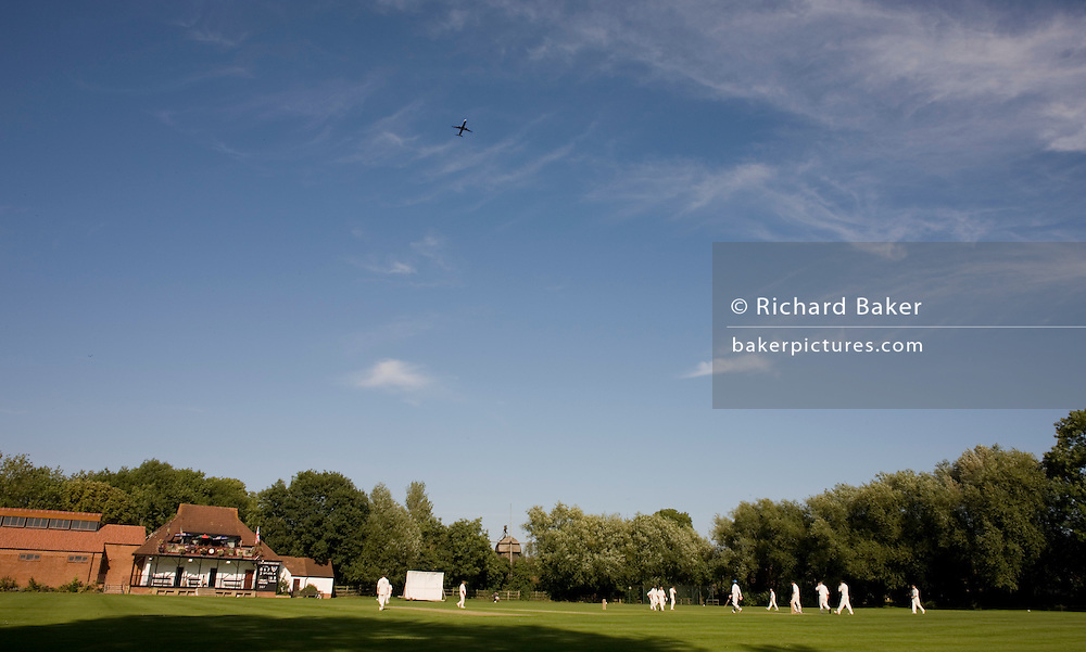 Players in a cricket match are oblivious to a passing airliner that passes overhead on a flight-path from Heathrow airport.