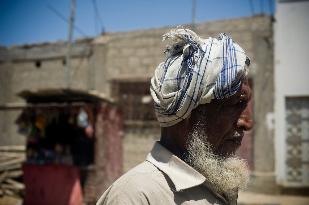 A man walks along the street in the blistering heat. Orangi town, Karachi, Pakistan, 2011