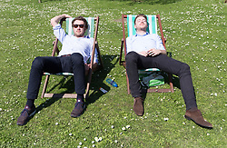 © Licensed to London News Pictures. 19/04/2018. London, UK. Two office workers relax in deckchairs during the hot weather in Regents Park in London at lunchtime today. Photo credit: Vickie Flores/LNP