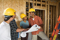 Couple consulting workers on construction site
