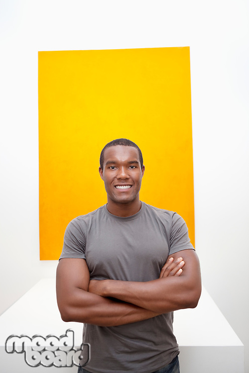 Half-length portrait of smiling young man in front of painting