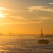 Silhouette of the Statue of Liberty in New York City during sunset
