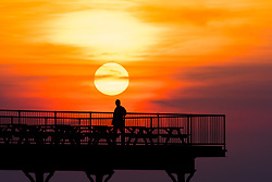 ©Licensed to London News Pictures. 11/04/2019.<br /> Aberystwyth, UK.  The sun sets as a spectacular golden globe behind people silhouetted as they stand at the end of the pier in Aberystwyth on the Cardigan Bay coast of west Wales. Credit: Keith Morris/LNP