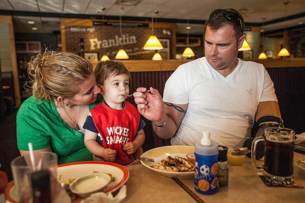 Injured Air Force Master Sgt. Joseph Deslauriers Jr. has lunch with his wife Lisa and their 17 month old son Cameron in Franklin, MA, during a visit home to Massachusetts on Monday, May 20, 2013. In 2011, Deslauriers lost both of his legs and part of an arm after stepping on an explosive device while stationed in Afghanistan. He is currently rehabbing at Walter Reed Army Medical Center.  (Matthew Cavanaugh for The Washington Post)
