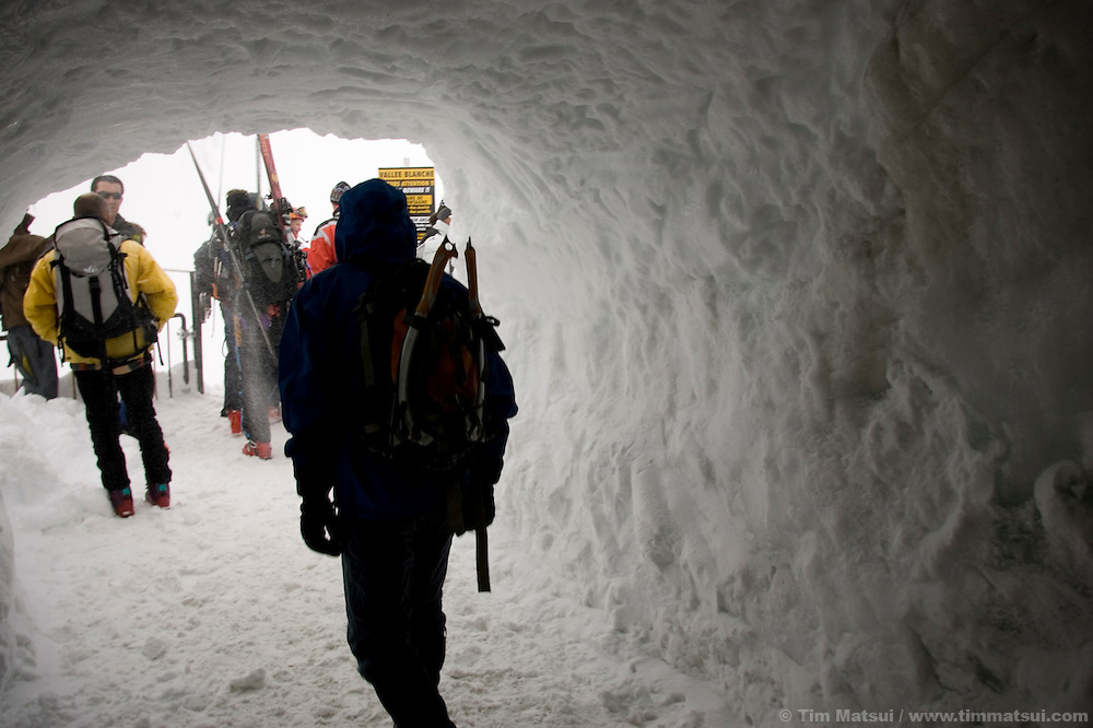Climbers descend from the Aguille du Midi tram in poor weather in Chamonix, France.