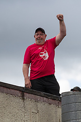© Licensed to London News Pictures . 13/05/2013 . Manchester , UK . Man wearing George Best t-shirt on top of a roof overlooking Sir Matt Busby Way . Manchester United trophy parade on Sir Matt Busby Way , from Old Trafford to Manchester City Centre this evening (Monday 13th May) . The team are celebrating their 20th league title win and commemorating the retirement of manager , Sir Alex Ferguson , by carrying the trophy on an opened top bus through the city . Photo credit : Joel Goodman/LNP
