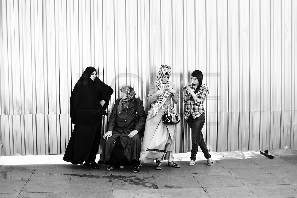 Four generations of turkish women waiting with different clothing in a street near New Mosque (Yeni Cami), in Istanbul.