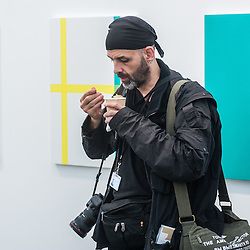 London, UK - 15 October 2014: a member of the press tastes the soup made with vegetables from Fukushima, Japan at the Green Tea Gallery during the first day of Frieze Art Fair and Frieze Masters in Regent's Park.