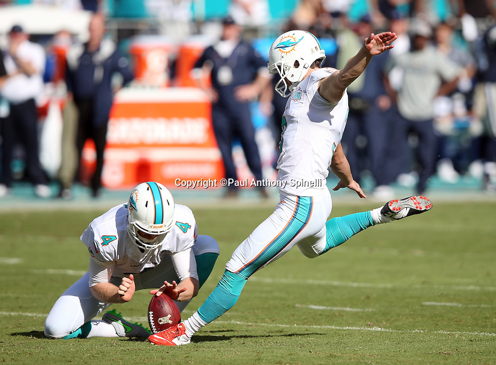 Miami Dolphins punter Matt Darr (4) holds while Miami Dolphins kicker Andrew Franks (3) kicks a second quarter extra point that cuts the Dallas Cowboys lead to 14-7 during the 2015 week 11 regular season NFL football game against the Dallas Cowboys on Sunday, Nov. 22, 2015 in Miami Gardens, Fla. The Cowboys won the game 24-14. (©Paul Anthony Spinelli)