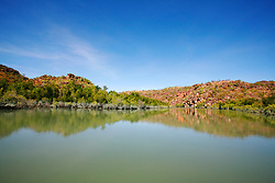 Mangroves are reflected in the still water on the Hunter River on the Kimberley coast.