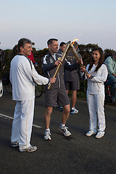 © Licensed to London News Pictures. 19/05/2012. Lands, UK. Steve Brady passes the Olympic Flame to 16 year old Vicky Smith between Lands End and Sennen. Photo credit : Ashley Hugo/LNP