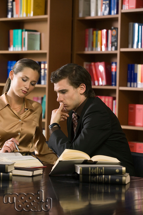 Young man and woman studying at desk in library