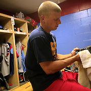 Infielder Ryan Peterson polishes his baseball cleats before the A's game with the Omaha Diamond Spirit.  It's a pre game ritual that extends from his high school and college teams.  photo by David Peterson