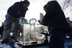 © Licensed to London News Pictures.10/01/2013. London, UK. Members of team Spain create an ice sculpture during the single block ice-sculpting competition at the London Ice Sculpting Festival in Canary Wharf.. Photo credit : Peter Kollanyi/LNP