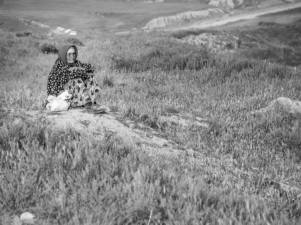 Portrait of an old Tajik woman sitting and watching her flock