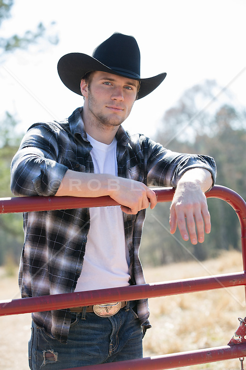 cowboy leaning against a fence on a ranch