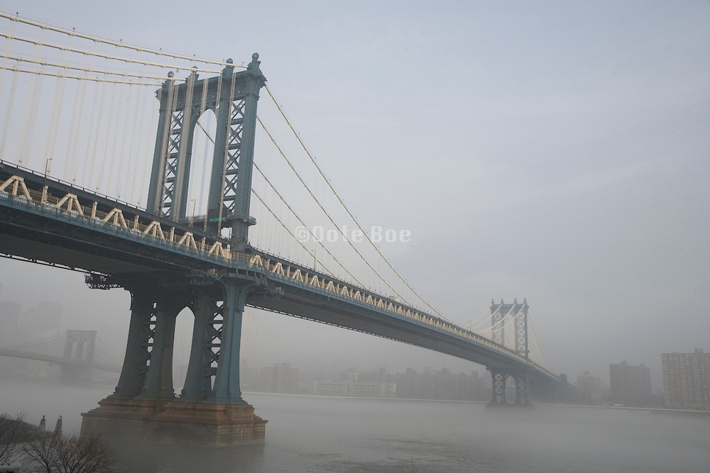 Manhattan Bridge with Brooklyn Bridge in the background during a morning fog