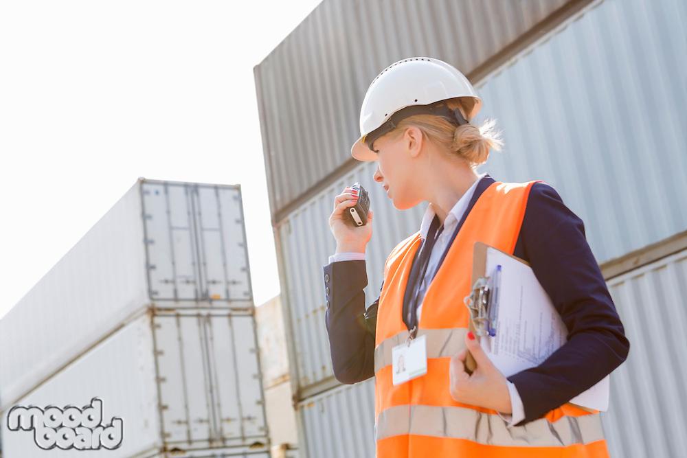Female engineer using walkie-talkie in shipping yard