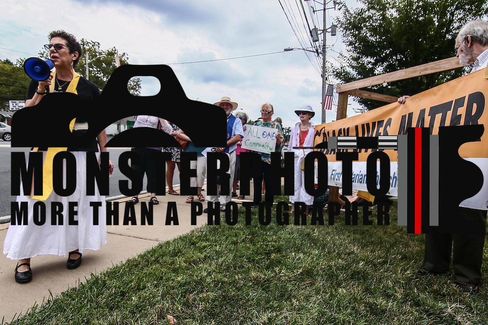 Rev. Roberta Finkelstein, Left,  gives remarks to a large crowd during a rededication ceremony for its Black Lives Matter banners Sunday, August 21, 2016, at First Unitarian Church in Wilmington.