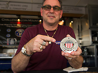 John Mottola shows off his mounted custom medals at his booth located outside at Laconia Harley Davidson.  (Karen Bobotas/for the Laconia Daily Sun)