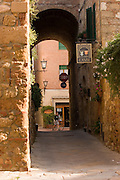 A rider walks his bike along a lane within the walled town of Pienza, Italy. Revisit with the Pellegrini family, 2005, Pienza, Italy. The Pellegrinis were Italy's participants in Material World: A Global Family Portrait, 1994 (pages: 198-199), for which they took all of their possessions out of their house for a family-and-possessions-portrait. In 1996, UNESCO declared the town a World Heritage Site.