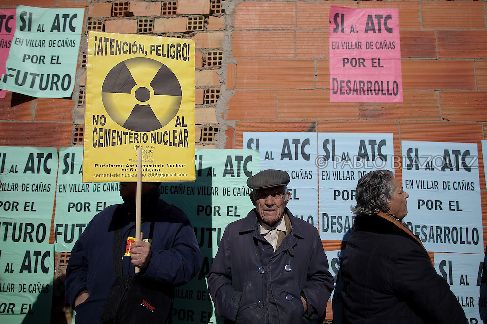 Two neighbors (R) stand next to a protester (L) during a demonstration organized by environmentalists against the possible construction of a nuclear waste storage in Villar de Cañas, near Cuenca , on February 12, 2012. Yellow placard reads 'Alert, danger. No to the nuclear cementary'. Green placards read ' OK for the ATC at Villar de Canas for the future'.