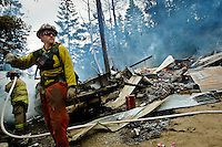 Casey McCormack, with Idaho Department of Lands, surveys the landscape before creating a fireline through the brush Thursday on Blossom Mountain, south of Post Falls. A secluded home was destroyed in the fire for which a cause has yet to be determined.