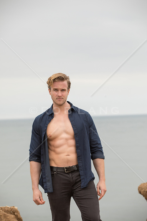 muscular man in an open shirt by the sea