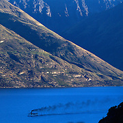 The TSS Earnslaw,  a 1912 Edwardian vintage twin screw steamer on the waters of Lake Wakatipu in, Queenstown, New Zealand. .It is one of the oldest tourist attractions in Central Otago, and the only remaining passenger-carrying coal-fired steamship in the southern hemisphere..The TSS Earnslaw heads along Lake Wakatipu from Queenstown  daily, running tourist trips to Walter Peak Station passing magnificent  peaks and contrasting shoreline foliage along the lakeside. Queenstown, New Zealand. 29th March 2011. Photo Tim Clayton