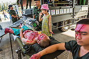 "11 JANUARY 2014 - BANGKOK, THAILAND: A Thai girl poses for family photos with mockups of battlefield casualties during Children's Day in Bangkok. The Royal Thai Army hosted a ""Children's Day"" event at the 2nd Cavalry King's Guard Division base in Bangkok. Children had an opportunity to look at military weapons, climb around on tanks, artillery pieces and helicopters and look at battlefield medical facilities. The Children's Day fair comes amidst political strife and concerns of a possible coup in Thailand. Earlier in the week, the Thai army announced that movements of armored vehicles through Bangkok were not in preparation of a coup, but were moving equipment into position for Children's Day.      PHOTO BY JACK KURTZ"
