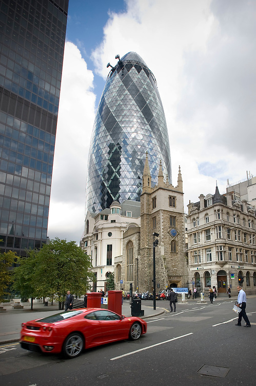 A Ferrari passes the Swiss Re building (Gherkin) in the City of London.
