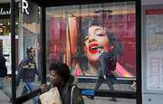A bus traveller eats in a bus shelter near a video loop for the London retailer 'Reserved', on Oxford Street, on 22nd November 2017, in London England.