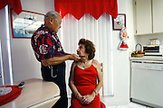 George Quiles helps his wife, Dora Quiles, do her hair in the kitchen of their Port Richey home on a Friday evening before they head out for a night of salsa dancing. George, a retired hairdresser, helps Dora with details including her make-up because she is legally blind and has trouble seeing well enough to perfect the job. Wearing matching outfits they coordinate each week, they spend the evening at the Tampa club Mirage tearing up the dance floor long after the rest of their other retired friends in their neighborhood have gone to bed. STORY SUMMARY - Floridian feature on Dora and George Quiles, a retired Port Richey couple who go salsa dancing twice a week at a club called Mirage in Tampa. The Quiles met in their youth in New York when an underaged Dora was standing at the bar, George tapped her on the shoulder and without saying a word made a twirling circular motion with his finger for her to spin around in front of him. He liked what they saw and they've been dancing ever since. They joke that most of their friends are couch potatoes and they don't want to become like that. So instead they grind on each other as she squeals and her husband occassionally grabs her butt. (Times photo by Brian Cassella)