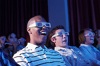 Young men wearing 3-d glasses watching 3-D movie in theatre