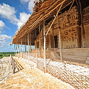 """Ornate carvings on the exterior of the Tomb of Ukit Kan Le'k Tok' at the ancient Mayan ruins at Ek'Balam, near Valladolid, Yucatan, Mexico. The jaguar is a recurring motif, as evidenced by the large stone teeth, etc. Ek' Balam means """"dark jaguar."""" The Acropolis towers above the surrounding countryside."""