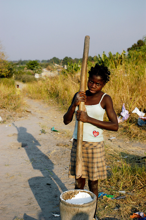 A young girl pounding cassava into meal in Luanga 1 village, an area cleared of landmines by Mines Advisory Group (MAG), to allow the resettlement of returning refugees after decades of civil war..Luau, Moxico Province, Angola. 25/07/2008..Photo © J.B. Russell