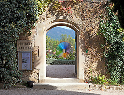 Entrance to the garden cocurtyard of the Chateau de Lourmarin has two separate buildings, one constructed around a courtyard in the 15th century and the other as a conjoined wing in the 16th century; the latter is furnished with notable antiques. It is open to the public for tours at appointed times and days, and is used as a concert and exhibition venue.