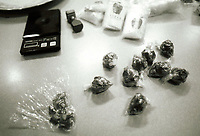 Bags of heroin, scale and stamp seized during a drug raid.