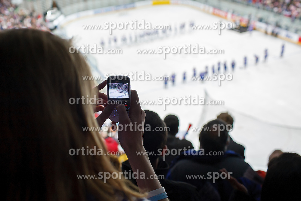 Girl taking photo of the players during national anthem at ice-hockey match between Slovenia and Ukraine at IIHF World Championship DIV. I Group A Slovenia 2012, on April 19, 2012 at SRC Stozice, Ljubljana, Slovenia. (Photo By Matic Klansek Velej / Sportida.com)