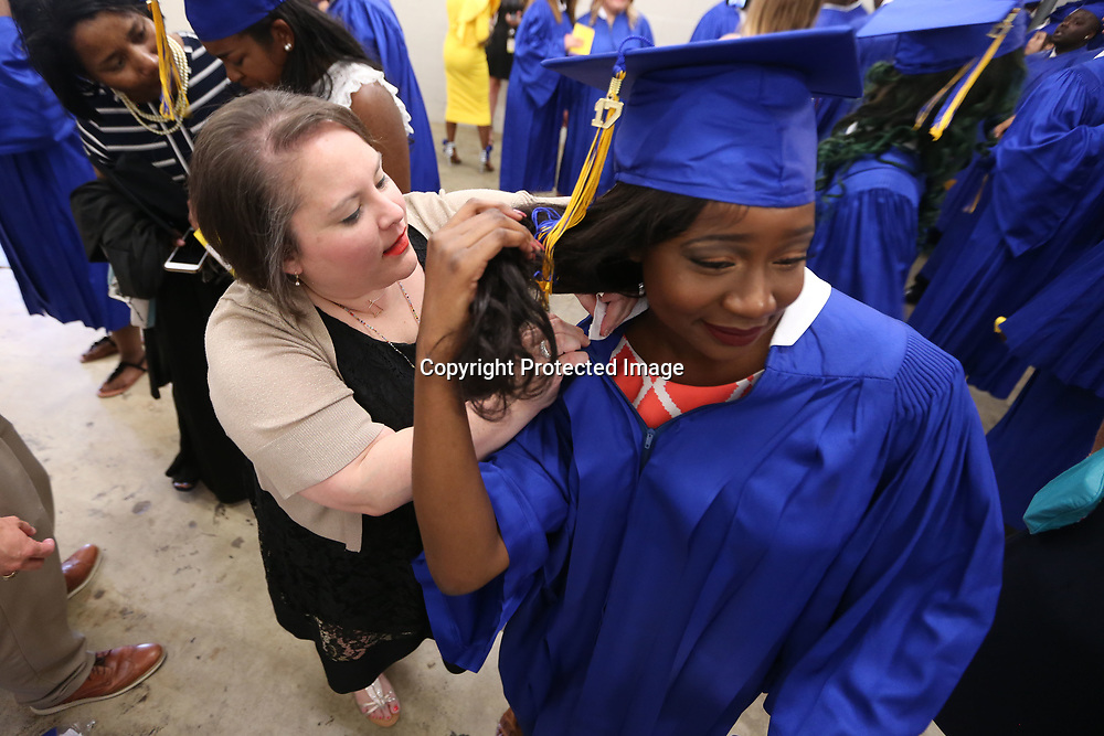 Allana Austion, drama teacher at Tupelo High School, helps student Keilah Roberts with her graduation gown prior to the start of the Tupelo High School graduation ceremony Friday night.