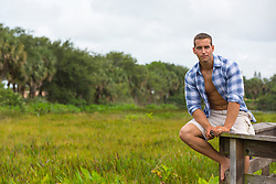 good looking 20 year old outdoors in The Everglades sitting on a wooden deck