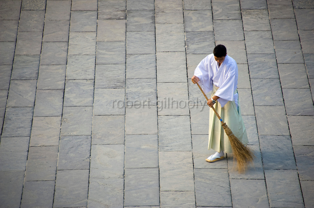 A shrine official sweeps the flagstone approach to the inner sanctuary of the shrine during the annual Reitaisai Grand Festival at Tsurugaoka Hachimangu Shrine in Kamakura, Japan on  14 Sept. 2012.  Sept 14 marks the first day of the 3-day Reitaisai festival, which starts early in the morning when shrine priests and officials perform a purification ritual in the ocean during a rite known as hamaorisai and limaxes with a display of yabusame horseback archery. Photographer: Robert Gilhooly