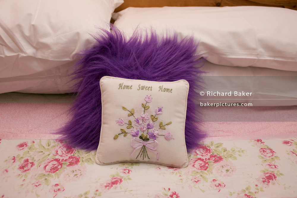 A fluffy 'Home Sweet Home' embroidered cushion is placed on a pink bedspread at the Roskhill guesthouse, Isle of Skye