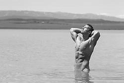 naked muscular man in a lake