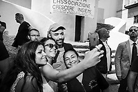 """NAPLES, ITALY - 30 JULY 2018: Roberto Saviano (center), an Italian journalist, writer and essayist poses for a selfie with some fans near the collective """"Nuovo Teatro Sanità"""" (New Sanità Theatre) in the Sanità neighborhood in Naples, Italy, on July 30th 2018.<br /> <br /> In 2017 the 17-year-old innocent victim Genny Cesarano was shot and killed by stray bullet  in cross fire between 2 rival gangs vying for territorial control in the Sanità neighborhood.<br /> The  isolation of the neighborhood Sanità over the years provided an ideal location for the Camorra to expand their illicit activities and profit from soaring unemployment rates and economic instability,<br /> <br /> After the first death threats of 2006 by the Casalese clan , a cartel of the Camorra, which he denounced in his exposé and in the piazza of Casal di Principe during a demonstration in defense of legality, Roberto Saviano was put under a strict security protocol. Since 2006 Roberto Saviano has lived under police protection.<br /> <br /> Saviano's latest novel """"The Piranhas"""", which tells the story of the rise of  a paranza (or Children's gang) and it leader Nicolas, will be released in the United States on September 4th 2018."""