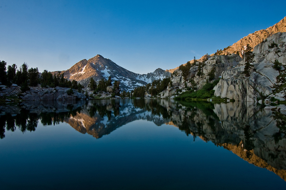 Reflections in the still early morning waters of Sixty Lakes Basin, high in the Sierra Nevadas of California