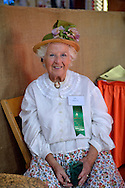 Old Bethpage, New York, USA. September 28, 2014. RUTH DEMARTINO is a volunteer wearing a traditional white blouse and flowered skirt and straw bonnet in the Exhibition Hall at the 172nd Long Island Fair, a six-day fall county fair held late September and early October. A yearly event since 1842, the old-time festival is now held at a reconstructed fairground at Old Bethpage Village Restoration.