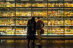 Visitors looking at  bottles of Scotch Whisky on display at the Scotch Whisky Experience visitor centre on the Royal Mile in Edinburgh, Scotland, UK